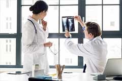 Ein Arzt und eine Ärztin besprechen eine Röntgenaufnahme