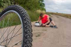 Gestürzte Radfahrerin hält sich verletztes Knie