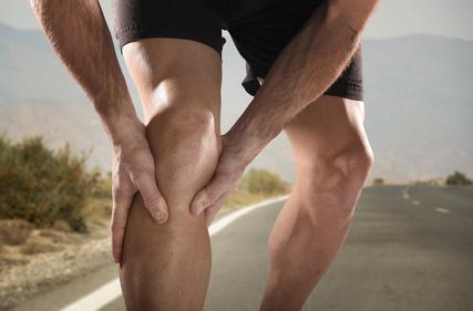 Junger, trainierter Läufer hält sich schmerzendes Knie