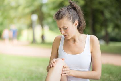 Junge Sportlerin mit Knieverletzung