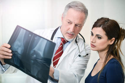 Arzt erklärt seiner Patientin die Röntgenaufnahme des Knies