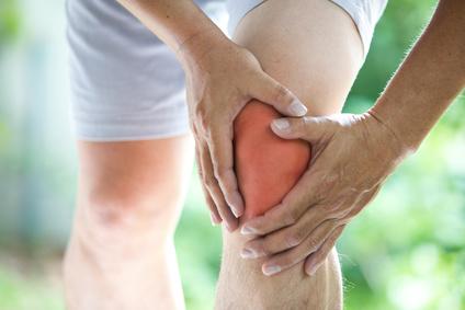 Jogger im Freien hält sich gerötetes Knie