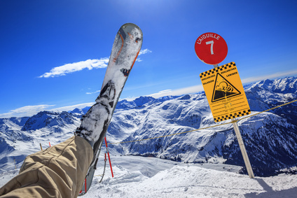 Nahaufnahme des linken Beins eines gestürzten Skifahrers am Rand eines Lawinengebiets