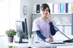 Medizinische Fachangestellte telefoniert und lächelt in die Kamera