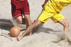 Nahaufnahme von zwei Strandfußballern im Zweikampf um den Ball